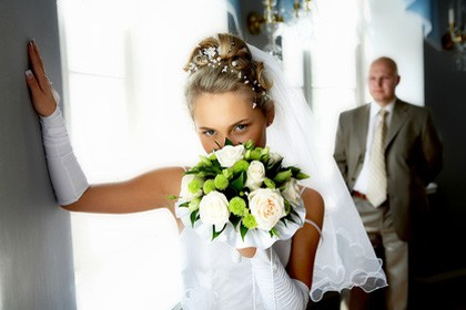 Bride holding Bouquet and Groom in background ready for entrance