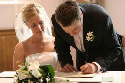 Couple signing wedding papers